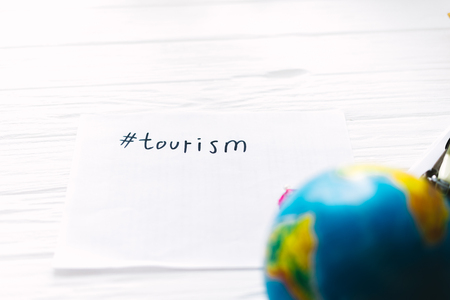 Inscription tour on a white sheet on a wooden background with a globe 写真素材 - 97773318