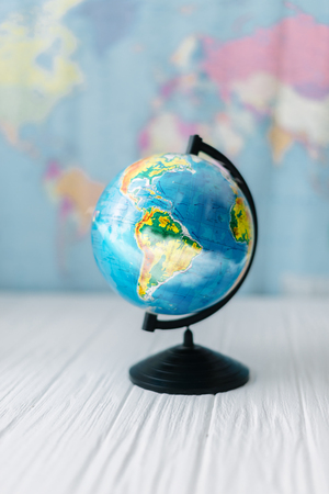 Globe on a wooden white table on the background of a world map