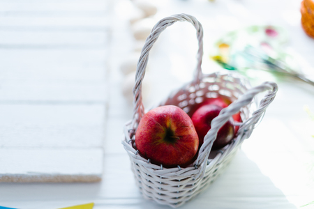 Red fresh apples in a white wooden basket.