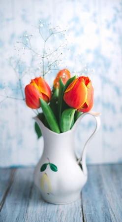 Tulips in a vase on a blue wooden background.