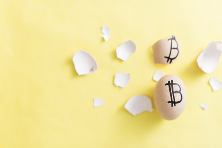 Egg with bitcoin painted on a yellow background. The concept of the collapse of the Crypto-currency.