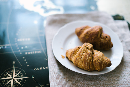 Croissant on burlap on the world map. The concept of food in the world.