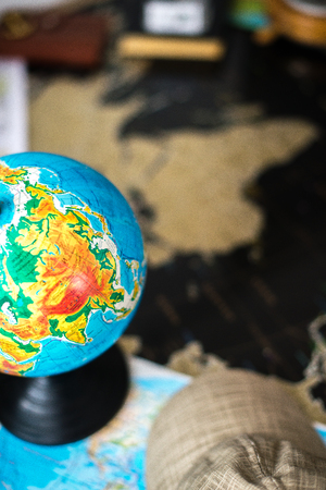 Globe on the black map of the world. The concept of traveling the world. Stock Photo