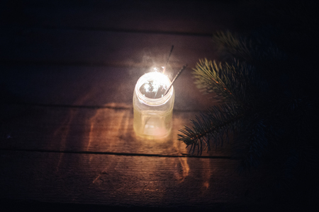 Bengal light in a glass jar on a wooden background with branches of a Christmas tree.