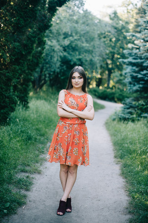 Beautiful young girl in a summer red dress in a park.