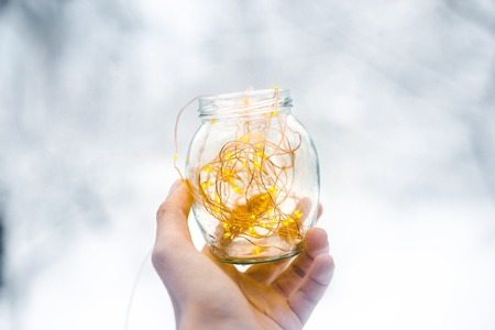 Glass jar with garlands in hand in winter.