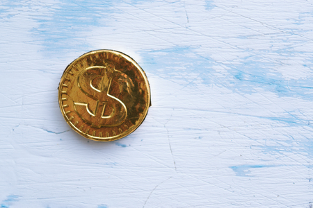 Coin sweet dollar on a wooden white background.