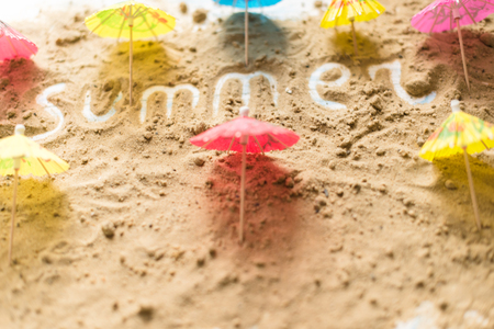 Summer inscription on a sandy background. The concept of travel.