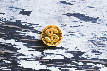 Coin sweet dollar on a wooden gray background. Stock Photo