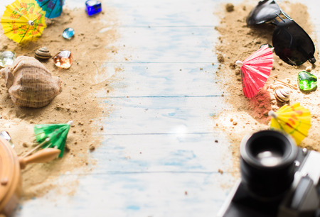 Beach still life. Black glasses with cocktail umbrellas, seashell on sand on a wooden background. Stock Photo