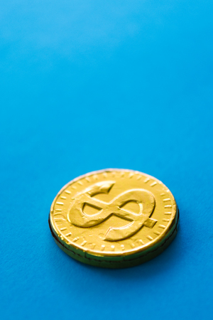 Gold dollar on a blue background. Concept of currencies.