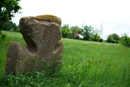 Old stone cross on a green meadow.
