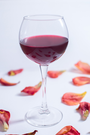 Red wine on a white background with rose petals.
