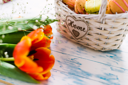 Blossoming tulips near a basket with macaroons. Stock Photo