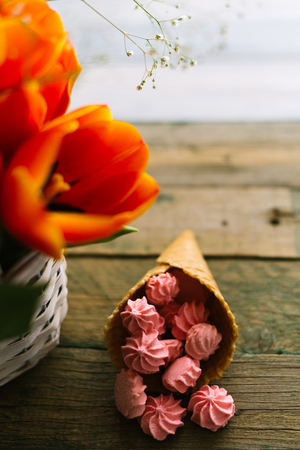 Blooming tulips near the horn with pink marshmallows. Stock Photo
