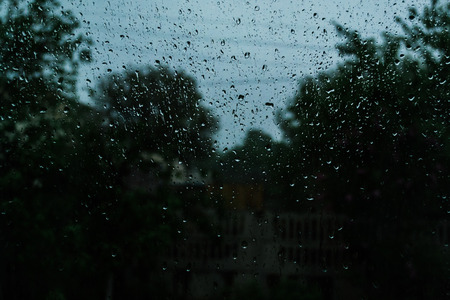 Rain drops on the window glass. Thunderstorm summer rain. Stock Photo