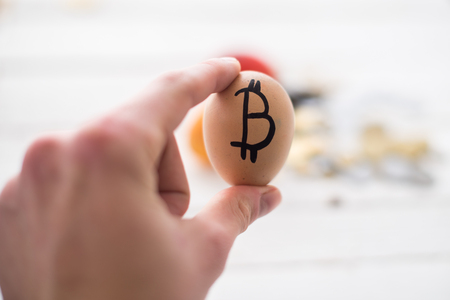 Egg with bitcoin in hand. The concept of Crypto-currency.