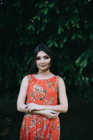 Beautiful young girl in a summer red dress in the park.