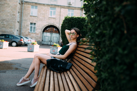 A girl in a black T-shirt and shorts in a park on a bench Stock Photo