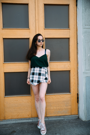 Beautiful young girl near an old door in sunglasses.