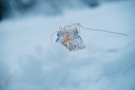 Glass jar with garlands in the snow on a blurred background