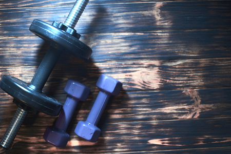 Dumbbells on a dark wooden background. Concept CrossFit.