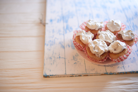 Cupcakes with white cream on a wooden background. Stock Photo