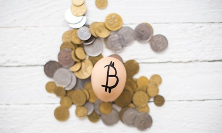 Eggs bitcoins on coins on a wooden background.