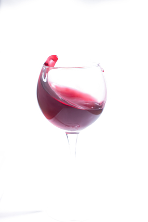 A glass with red wine on a white background. Isolate.