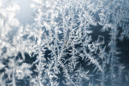 Frosty patterns on the frozen window are macro. Winter background. Stock Photo