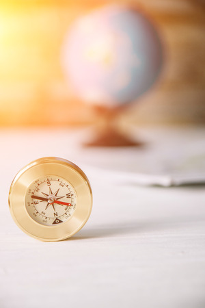 Compass on a white wooden table with a blurred background Stock Photo
