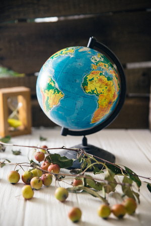 Globe on wooden white boards with a blurred background. Autumn still life. Stock Photo