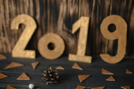 Golden numbers 2019 on a wooden old background.