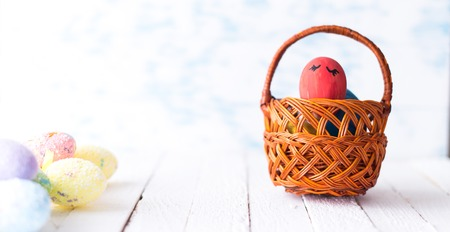 Easter eggs in a basket on a wooden background.