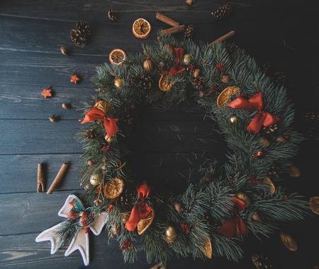 Natural Christmas wreath on black wooden background.