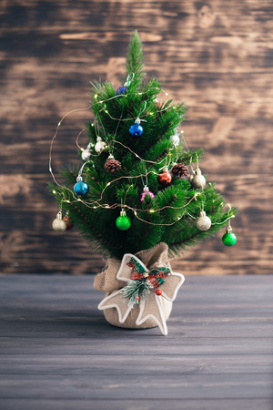 Christmas tree on a wooden blurred background.