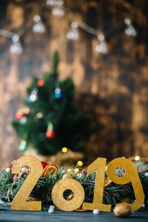 The inscription 2019 on the background of New Years decorations on a wooden background.