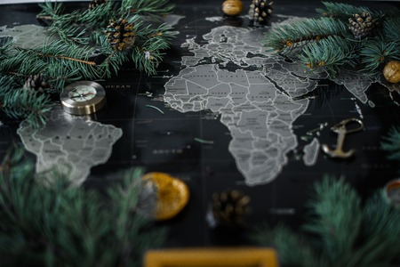Christmas tree branches and compass on a black map. Stock Photo