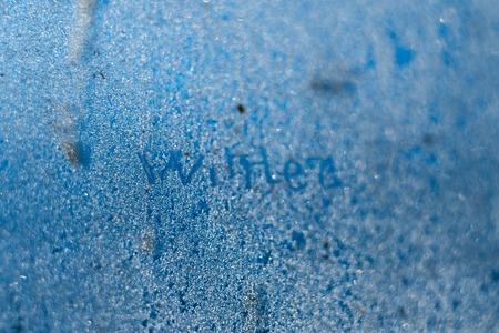 The inscription: winter on a frozen winter window. Background.