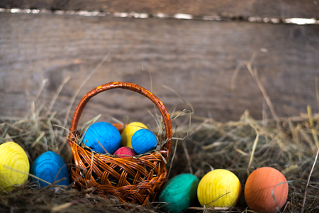 Easter eggs in a basket on a hay with a blurred background.