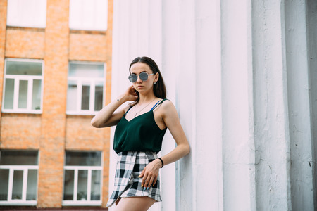 Sexy girl in sunglasses, t-shirt, and short shorts near the columns