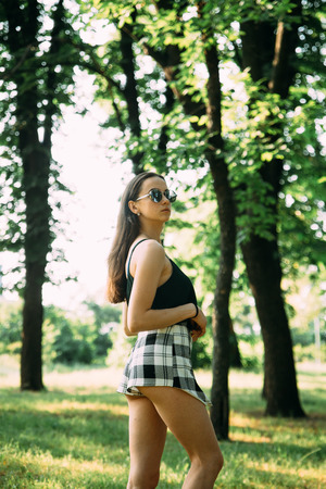 Beautiful young girl in a park in sunglasses.