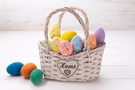 Easter eggs in a white basket on a white wooden background.