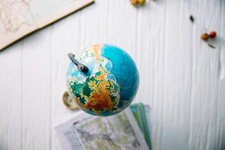Globe on wooden white boards. Flat lay.