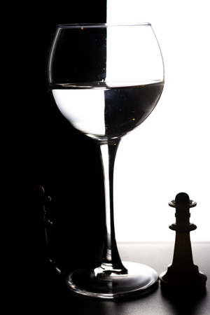 Glass of water with overlap in the form of a chessboard concept.