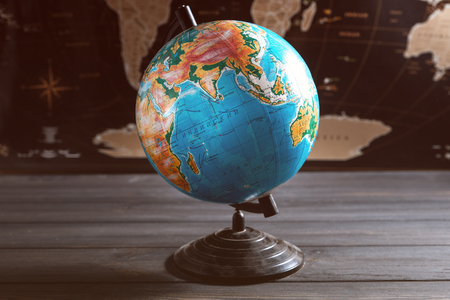 Geographical globe on the background of a black world map. Stock Photo