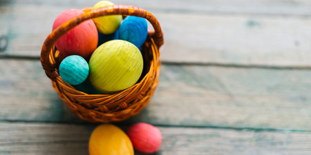 Colored easter eggs in a basket on a wooden background.