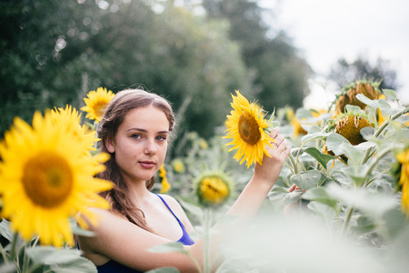 Beautiful girl on the field with sunflowers in short shorts and a vest.