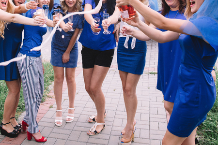 Bachelorette party, girls in blue dresses with glasses of champagne are having fun. Stock Photo