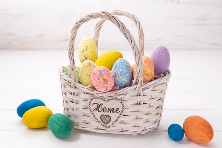 Easter eggs in a white basket on a white wooden background. Stock Photo